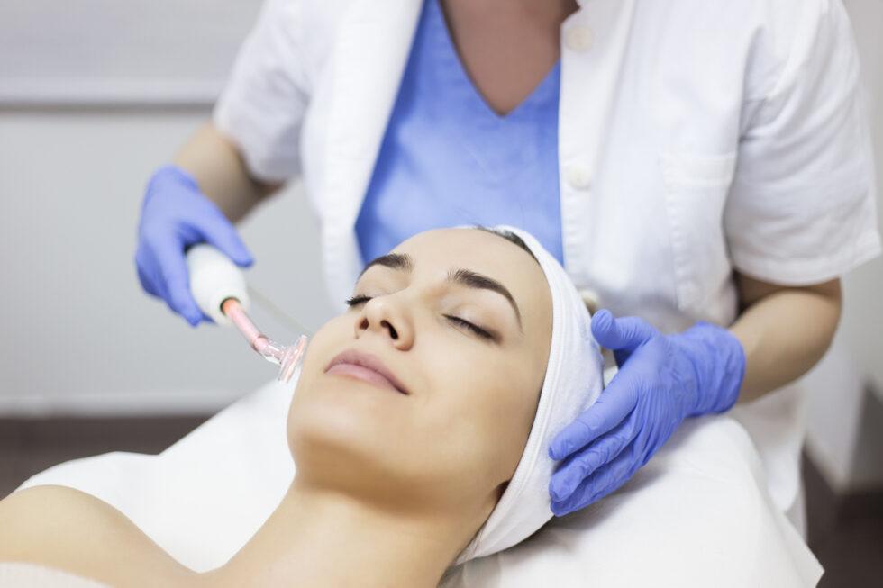 ozoniranje lica, doktorka radi dezinfekciju lica ozonom i viskokom frekvencom, devojka na tretmanu ozoniranja lica