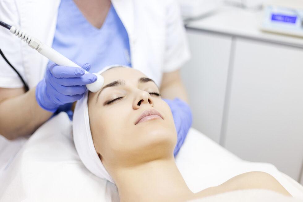 neinvazivna mezoterapija lica za akne, tretman mezoterapije aparatom, devojka na tretmanu lica