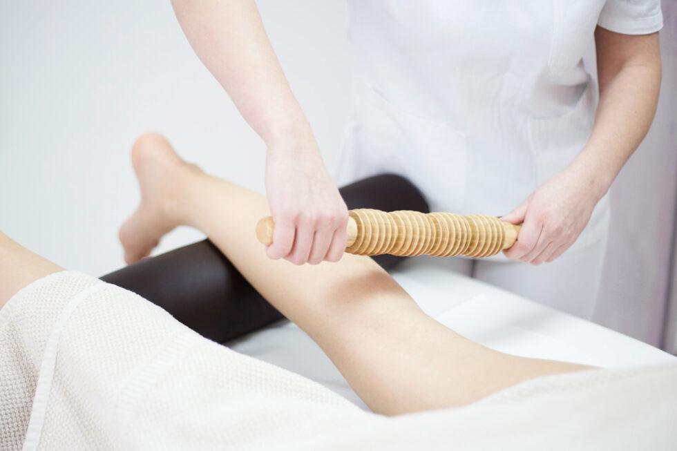 maderoterapija nogu, oklagija za maderoterapiju, terapeut izvodi masažu oklagijama